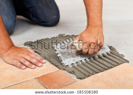 Worker hands spreading adhesive for ceramic floor tiles - closeup - stock photo