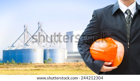 Worker holding a helmet with background of factory exterior - stock photo