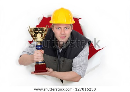 Worker holding a trophy cup. - stock photo