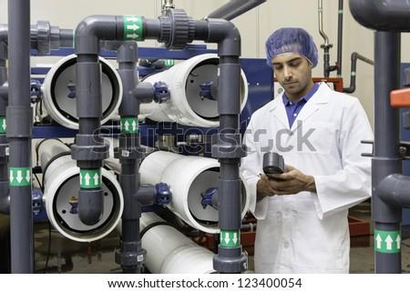 Worker holding an equipment in bottling plant - stock photo