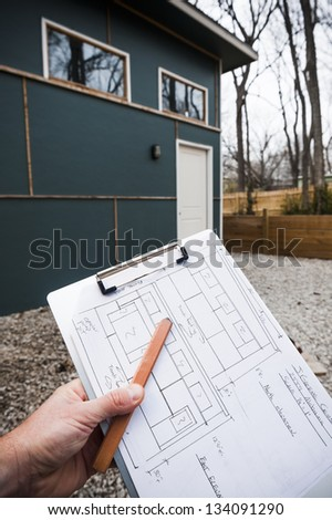 worker holding blue prints for the building in the background - stock photo