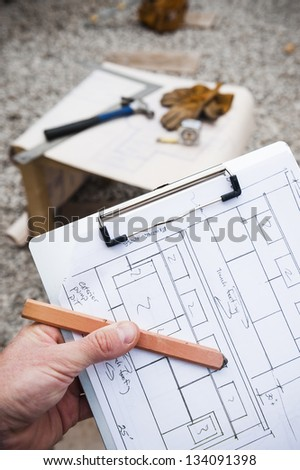 worker holding construction blue prints - stock photo