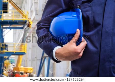 Worker holding his helmet - stock photo