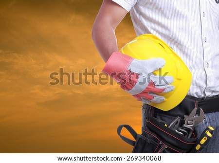 Worker holding tool with Twilight time on Labour Day - stock photo