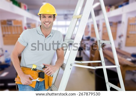 Worker holding tools while leaning on step ladder against workshop - stock photo