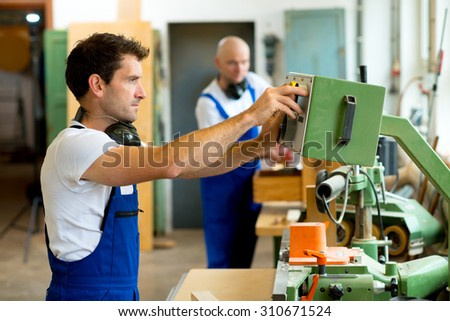worker in a carpenter's factory using machine - stock photo