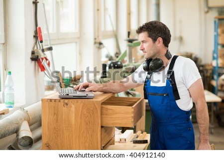worker in a carpenter's workshop using computer - stock photo