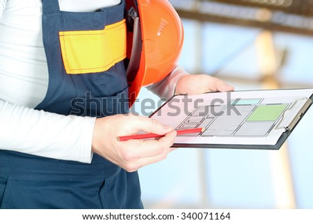 Worker in a construction site holds a project of a flat - stock photo