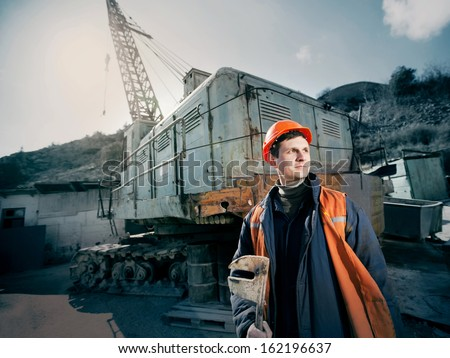 worker in a helmet with a wrench in his hand standing near a construction crane lifting