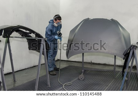 Worker in a paint booth. - stock photo