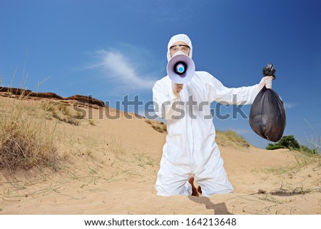 Worker in a protective suit holding a waste bag and warning via megaphone outside