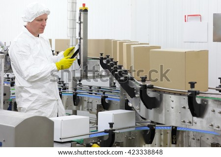 worker in apron, cap with tablet, at production line in factory - stock photo