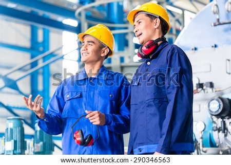Worker in Asian manufacturing plant discussing in front of machines
