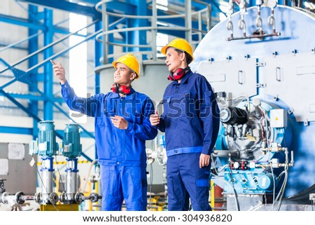 Worker in Asian manufacturing plant discussing in front of machines - stock photo