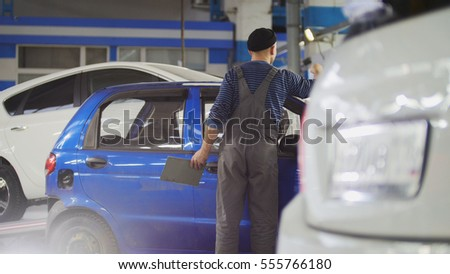 Worker in auto service preparing car for professional diagnostic, close up