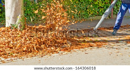 Worker in autumn with a leaf blower - stock photo
