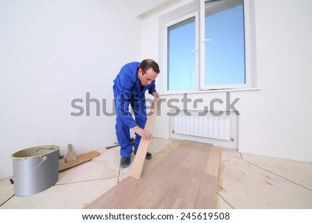 Worker in blue overalls laid wood parquet in white room - stock photo