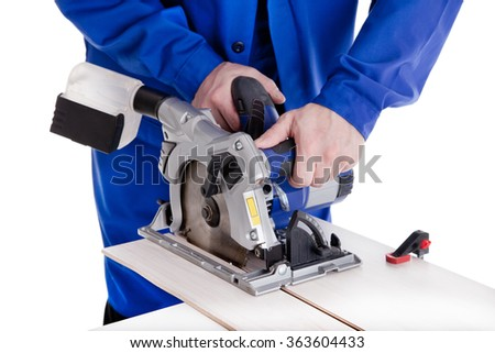 Worker in blue uniform cutting laminate with circular power saw, isolated on white