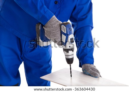 Worker in blue uniform using battery screwdriver, isolated on white - stock photo