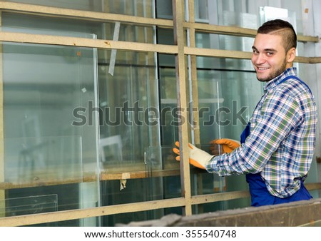 Worker in coverall  cutting glass for windows at workshop