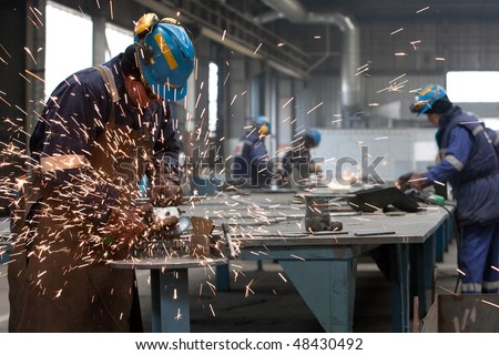 worker in factory grinding metal - stock photo