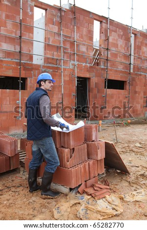 Worker in front of a site plan - stock photo