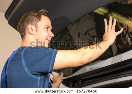 Worker in garage tinting a car window with tinted foil or film - stock photo