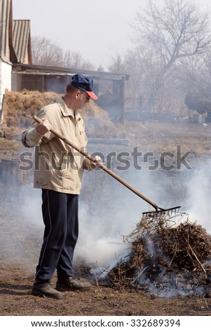 Worker in garden. Man rake burning dried leaves. Work on farm. Harvest time - stock photo