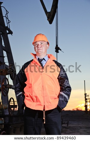 Worker in orange uniform and helmet on of background the pump jack and sunset sky. Severe. Hands in pockets. - stock photo