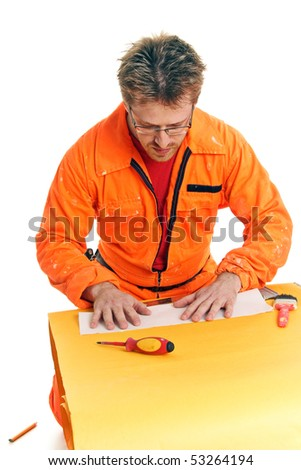 worker in orange work-wear carefully folds a paper sheet, isolated on white - stock photo