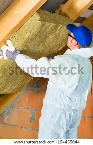 Worker in overall is setting thermal insulating material with gloves in the roof - stock photo