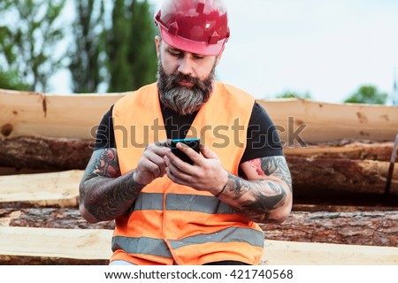 Worker in overalls and with a tattoo are checking the quality of materials and other inspections, makes recording on your mobile phone
