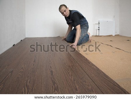 Worker in overalls puts laminate brown indoors