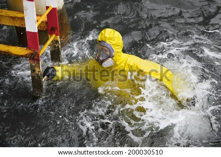 worker in professional, protective suit in ocean water  trying to reach  ladder to save his life  - stock photo