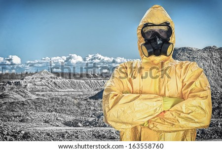 Worker in protective chemical suit over mountains. - stock photo