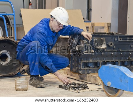 worker in protective clothes repairs the automobile mechanism - stock photo