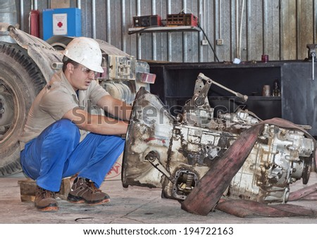 worker in protective clothes repairs the automobile mechanism