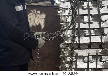 worker in protective gloves in factory stock of aluminium sheet metal profiles  - stock photo