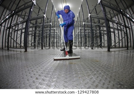 worker in protective overalls cleaning floor in empty storehouse - fish-eye lens - stock photo
