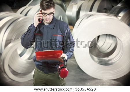 worker in protective uniform and protective ear muffs in front of sheet tin metal rolls in production hall - toned image, retro film filtered in instagram style - stock photo