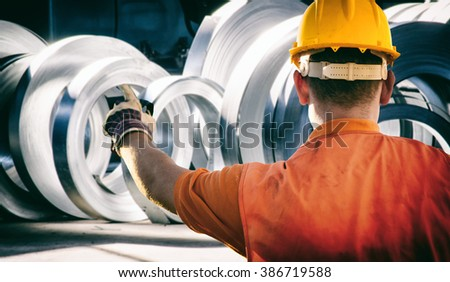 worker in protective uniform and protective helmet in front of sheet tin metal rolls in production hall - toned image, retro film filtered in instagram style - stock photo