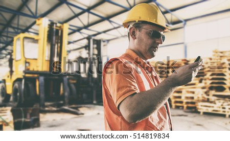 Worker in protective uniform and protective helmet with smart phone in production hall in front of forklift - toned image, filtered in instagram style