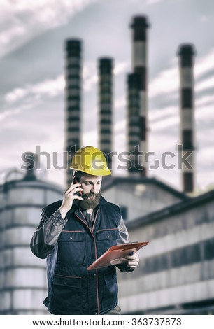 Worker in protective uniform in front of industrial chimney - toned image, retro film filtered in instagram style