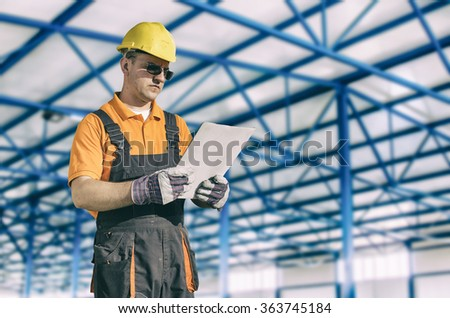 Worker in protective uniform in production hall - toned image, retro film filtered in instagram style - stock photo