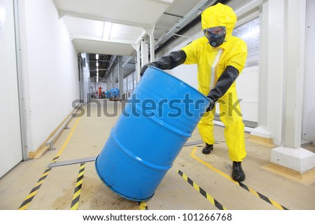 Worker in protective uniform,mask,gloves and boots rolling barrel of chemicals - stock photo