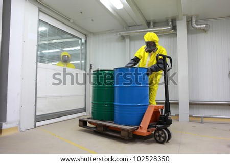 Worker in protective uniform,mask,gloves and boots working with barrels of chemicals on forklift ,another is observing hi, - stock photo