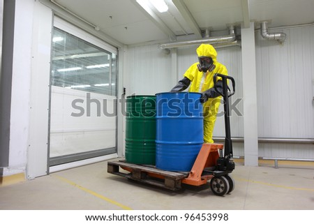 Worker in protective uniform,mask,gloves and boots  working with barrels of chemicals on forklift - stock photo