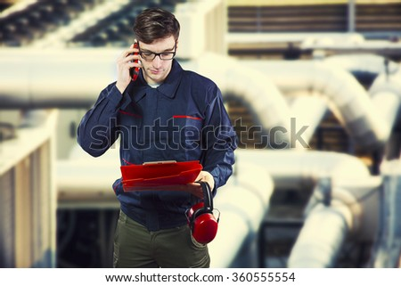 worker in protective uniform with smartphone, clipboard and ear muffs in front of industrial pipes - toned image, retro film filtered in instagram style - stock photo