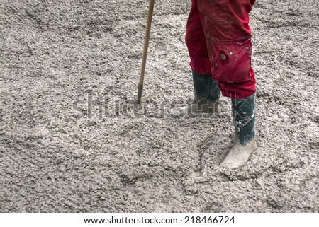 Worker in red and green boots flattens concrete with rake - stock photo