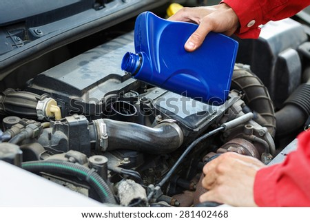 Worker in red overalls checking the oil in car. Detail of hands. - stock photo